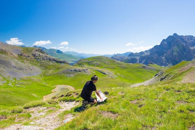 Viandante che legge la mappa di trekking al punto panoramico della montagna