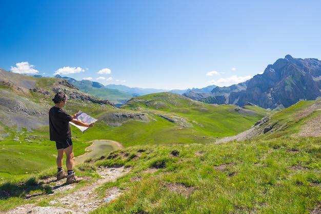 Viandante che legge la mappa di trekking mentre riposa al punto panoramico della montagna