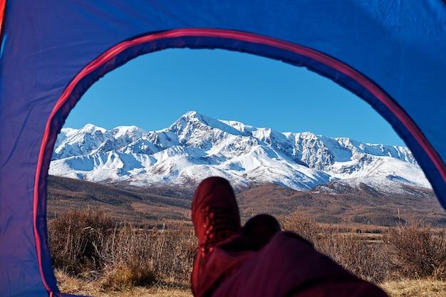 Viandante che si rilassa godendo della vista dall'entrata di campeggio della tenda all'aperto. vacanze di avventura di concetto di stile di vita di viaggio all'aperto.