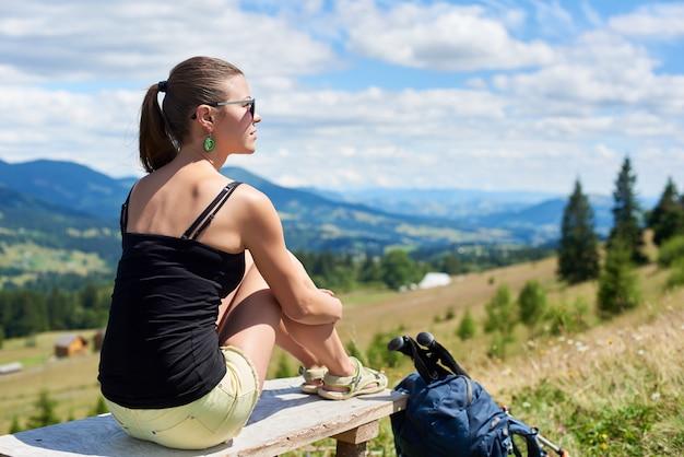 Viandante della donna che fa un'escursione sulla collina erbosa, indossando zaino, usando bastoncini da trekking in montagna