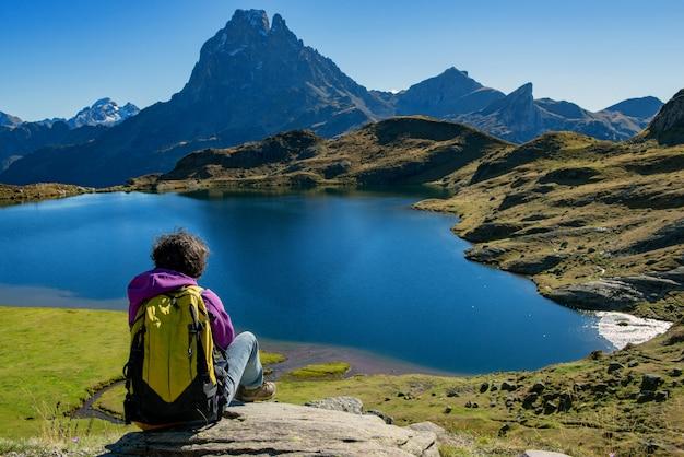Viandante della donna che si siede nelle montagne dei pirenei vicino al pic du midi d ossau