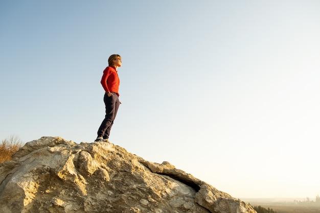 Viandante della giovane donna che sta da solo sulla grande pietra in montagne di mattina. turista femminile sull'alta roccia in natura selvaggia. concetto di turismo, viaggi e stile di vita sano.
