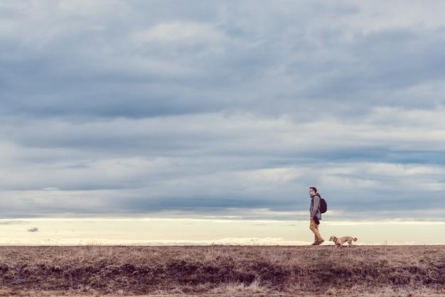 Viandante e cane che camminano nel pascolo