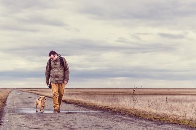 Viandante e cane che camminano sulla strada