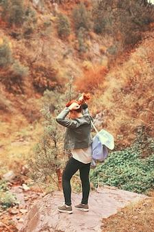 Viandante femminile che cammina nella foresta delle montagne.