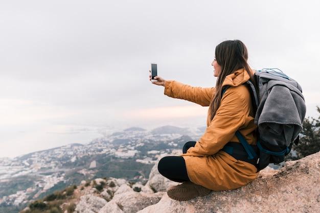 Viandante femminile giovane sorridente che si siede sopra la montagna che prende selfie sul telefono cellulare