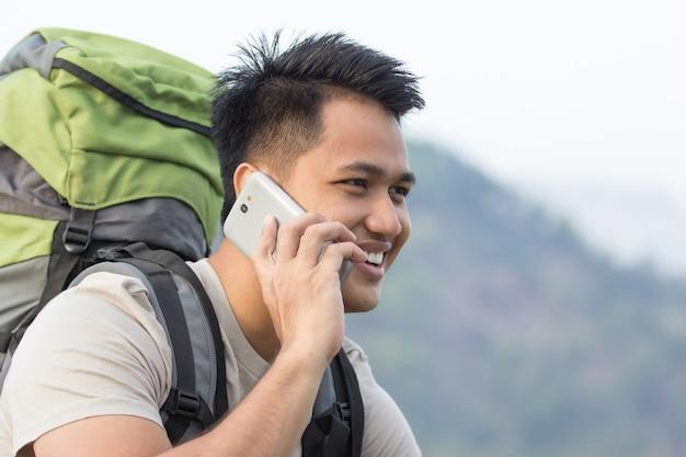 Viandante maschio che per mezzo del telefono cellulare