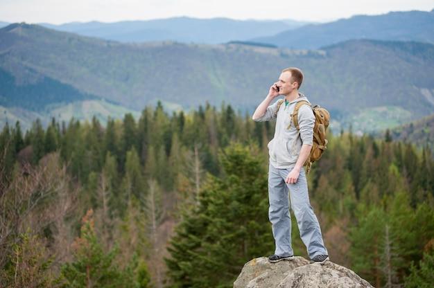 Viandante maschio con lo zaino che sta sopra una montagna che distoglie lo sguardo e che parla sul telefono sui precedenti vaghi di forest valley e delle colline.