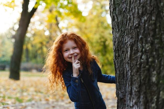 Vibrazioni autunnali, ritratto del bambino. la piccola ragazza affascinante e rossa sembra felice camminando e giocando su t