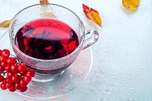 Viburnum di bacche rosse e tazza di tè