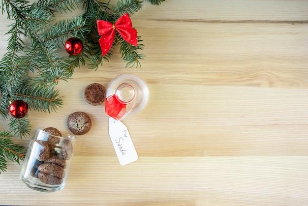 Vicino a decorazioni natalizie, bicchiere di latte e biscotti lasciati appositamente per babbo natale.