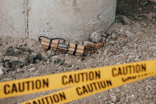 Vicino al supporto del ponte. esplosivo pericoloso steso a terra. nastro giallo di avvertenza davanti