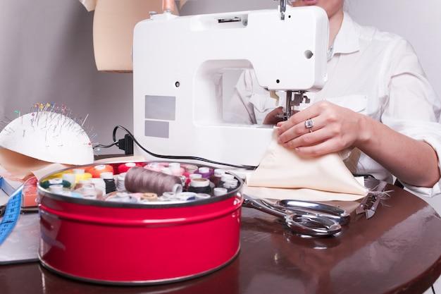 Vicino colpo di mani di una donna, che è impegnata a cucire in casa