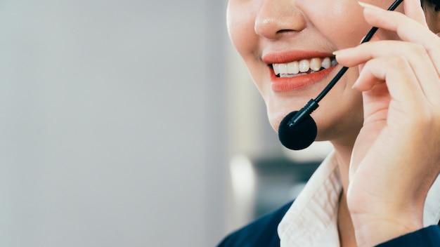 Vicino del personale asiatico giovane bella donna al banco di servizio parlando al telefono vivavoce in un call center