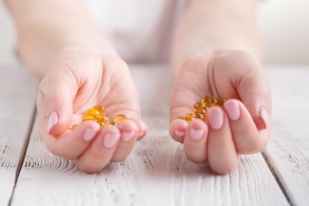 Vicino delle mani della donna che tengono le pillole o le capsule dell'olio di pesce a casa