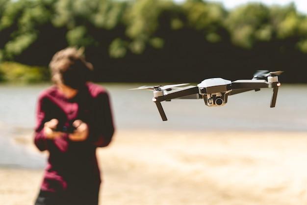 Vicino drone volante in aria con l'uomo con controller sullo sfondo.