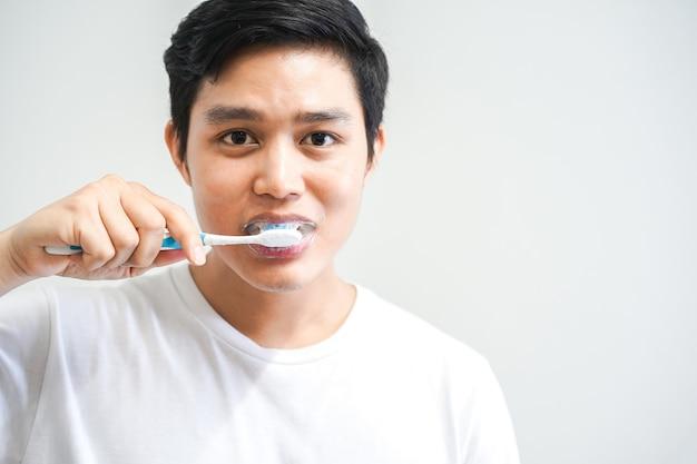 Vicino giovane uomo asiatico lavarsi i denti in bagno al mattino