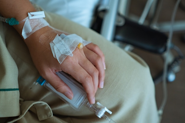 Vicino la mano del paziente con flebo medica o flebo iv in reparto ospedaliero, assistenza sanitaria medica
