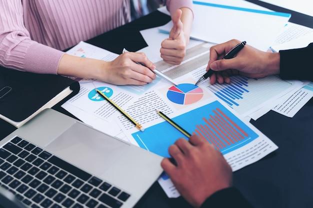 Vicino la mano di uomo d'affari impegnato alla scrivania su notebook e documenti di lavoro