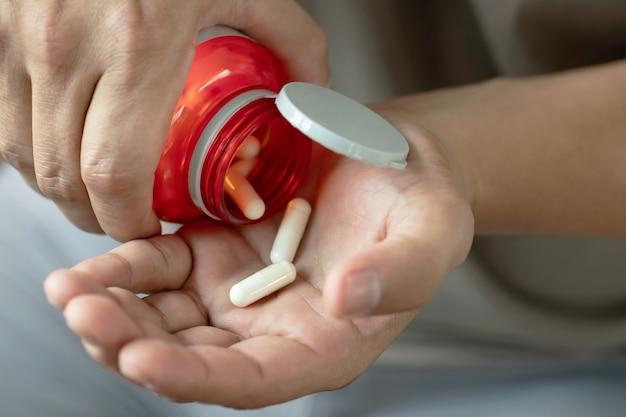Vicino man mano che regge una medicina, con versa le pillole dalla bottiglia. farmaco.