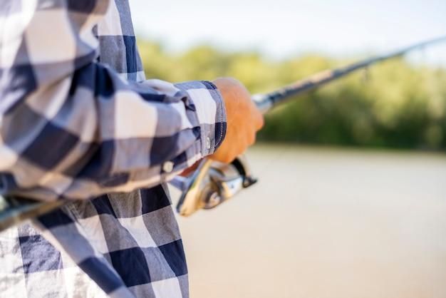 Vicino mani maschili che pescano pesce con filatura sulla riva del fiume.
