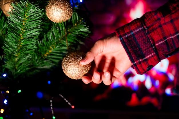 Vicino mano decorare l'albero di natale con i giocattoli a casa.