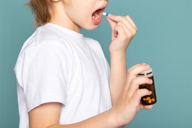 Vicino, vista bambino ragazzo biondo dolce adorabile carino prendendo pillola in maglietta bianca sulla scrivania blu