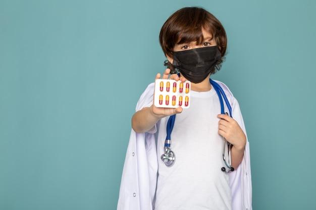 Vicino, vista bambino ragazzo carino adorabile tenendo le pillole in abito bianco sulla scrivania blu
