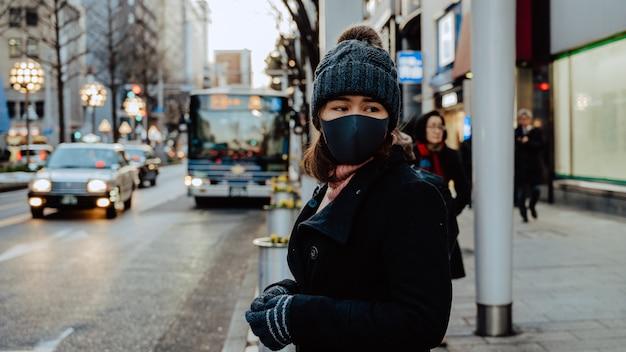 Vicino volto del viaggio turistico donna asiatica in giappone indossando la maschera. concetto di viaggio del virus dell'influenza del coronavirus