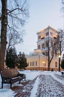 Vicolo invernale con una panchina e una torre dell'orologio nel parco