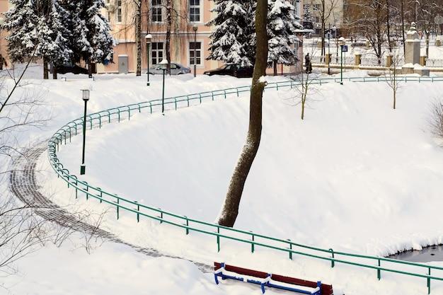 Vicolo nevoso curvo nel parco della città.