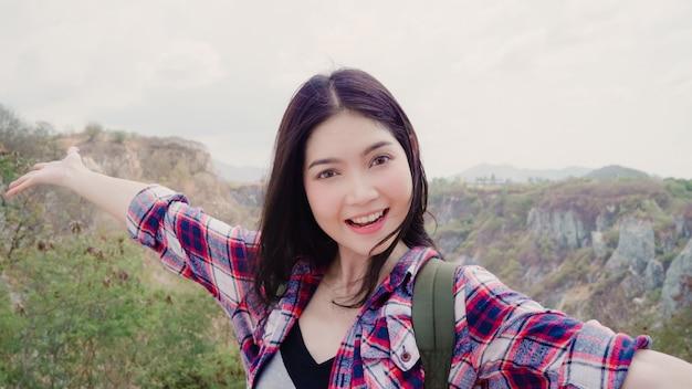 Video asiatico del vlog del record della donna di viaggiatore con zaino e sacco a pelo di blogger sopra la montagna