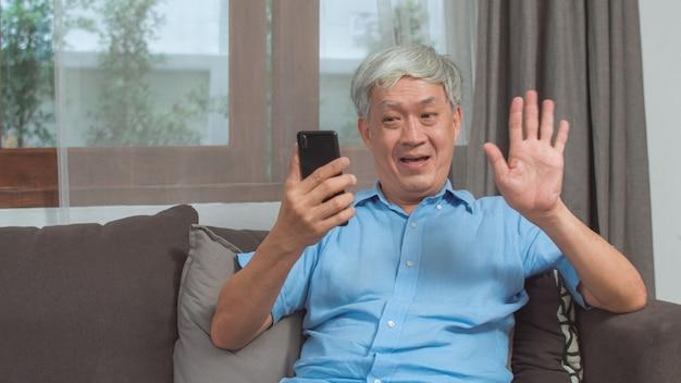 Video chiamata asiatica dell'uomo senior a casa. il maschio cinese più anziano senior asiatico che utilizza la videochiamata del telefono cellulare che parla con il nipote della famiglia scherza mentre si trova sul sofà nel concetto del salone a casa.