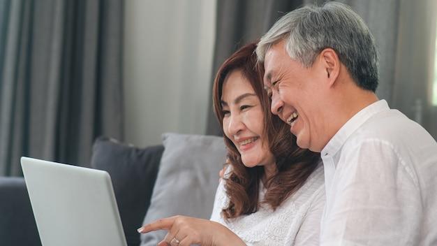 Video chiamata senior asiatica delle coppie a casa. i nonni cinesi senior asiatici, facendo uso della video chiamata del computer portatile che parlano con il nipote della famiglia scherzano mentre si trovano sul sofà nel concetto del salone a casa.