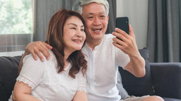 Video chiamata senior asiatica delle coppie a casa. i nonni cinesi senior asiatici, facendo uso della video chiamata del telefono cellulare che parlano con il nipote della famiglia scherzano mentre si trovano sul sofà nel concetto del salone a casa.