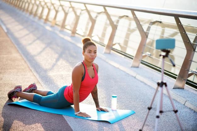 Video sullo yoga. blogger sportivo che indossa abbigliamento sportivo che realizza video sullo yoga all'esterno