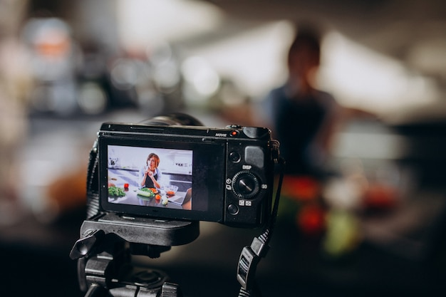 Videoblogger della giovane donna che cucina alla cucina e alle riprese