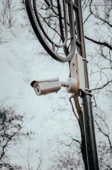 Videocamera di sorveglianza bianca che appende su un palo. la telecamera osserva l'ordine nelle strade e nei parchi. macchina fotografica su una posta in un parco. vista laterale e diritta