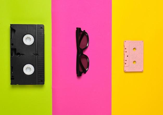 Videocassetta, occhiali da sole, cassetta audio su una superficie di carta multicolore. tendenza minimalista, piatto, vista dall'alto.