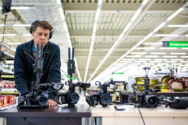 Videografo che gira un film o un programma televisivo in uno studio con una macchina fotografica professionale, nel backstage