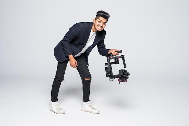 Videografo indiano professionale dell'uomo con il video slon ronin del gimball isolato sul fondo dello studio