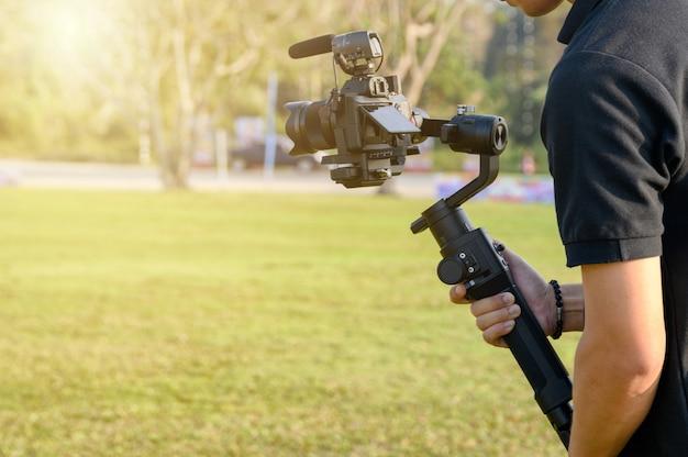 Videografo professionista con fotocamera su stabilizzatore cardanico per l'assunzione