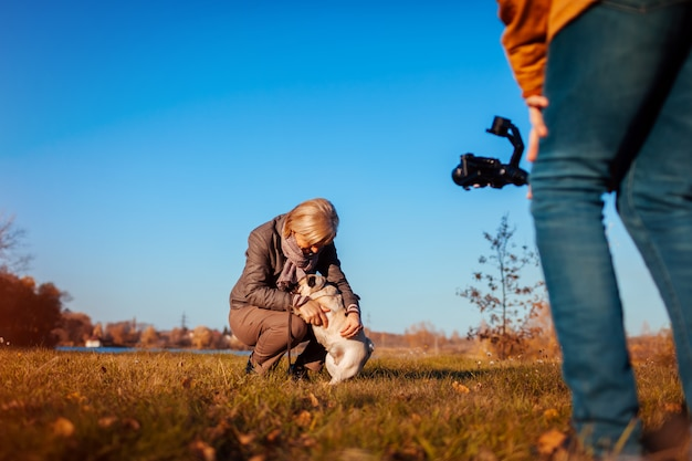 Videografo riprese donna con cane nel parco in autunno uomo che usando steadicam e macchina fotografica per fare filmati