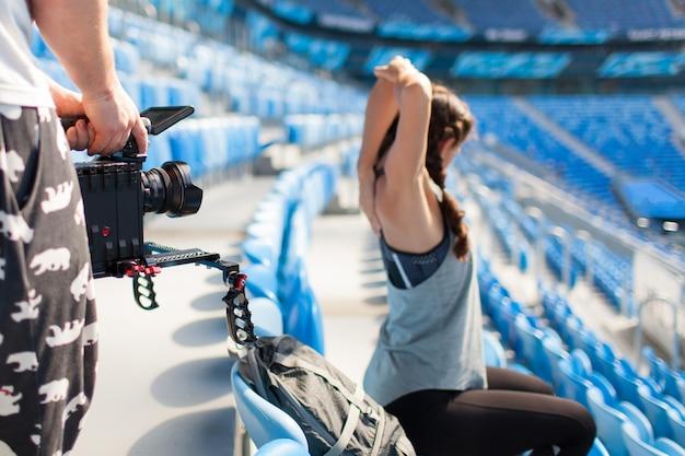 Videografo spara a una ragazza su una fotocamera professionale.