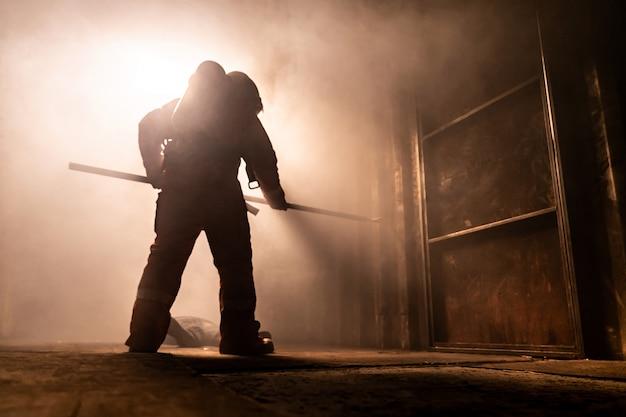 Vigile del fuoco che cerca di rompere una porta per fuggire dall'edificio in fiamme