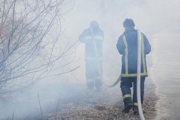 Vigile del fuoco due in fumo battaglia incendi boschivi. il pompiere coraggioso va in fumo per spegnere un fuoco selvaggio, altri vigili del fuoco tengono e trasportano il tubo