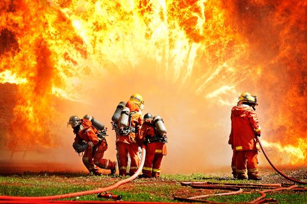 Vigili del fuoco che utilizzano estintore e acqua per il fuoco di combattente durante l'allenamento di lotta contro gli incendi.