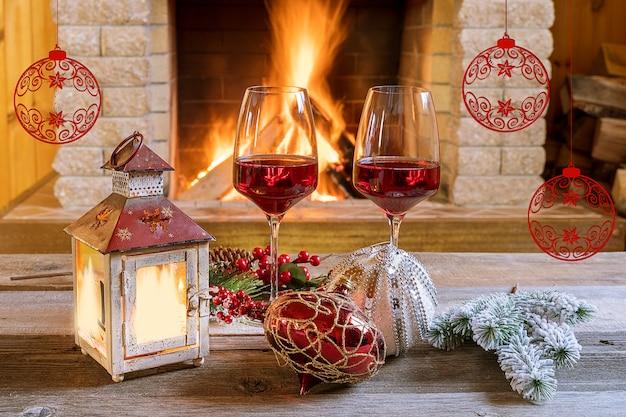Vigilia di natale. due bicchieri di vino e lanterna di natale vicino al camino accogliente, in casa di campagna.