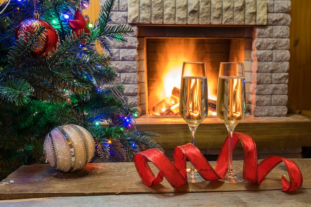 Vigilia di natale. il vino di champagne su una tavola vicino al camino accogliente prima dell'albero di natale ha decorato i giocattoli e le luci di natale in casa di campagna.