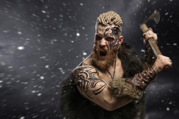 Viking vestito con la pelle di un orso che attacca con un'ascia